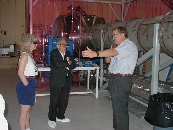 Fred Raab showing Wheeler and Kip Thorne's wife Carolee the interior of the LVEA building. That's  the evacuated beam tube behind them. Laser safety goggles for everyone here.