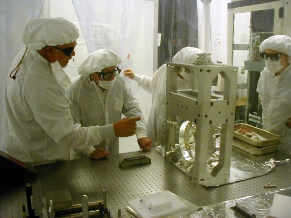 Doug Cook (I think) showing Wheeler on of the LIGO optics in the bake room.