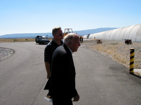 "Wheeler being shown around the LIGO Hanford grounds by Mark ""Ski"" Lubinski. That's the protective concrete cover for the evacuated beam tube. That cover runs off in the distance 2.4 miles."