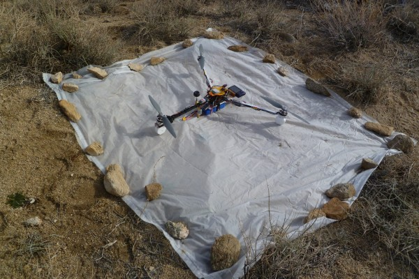 The assembled APM tricopter at a remote desert test area. The white plastic sheet keeps sand from being blown into the camera during takeoffs and landings.