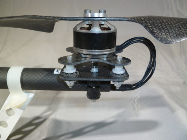 A closeup of one of the front arm's motor vibration isolation mounts. The motor is floating on four elastomeric grommets.