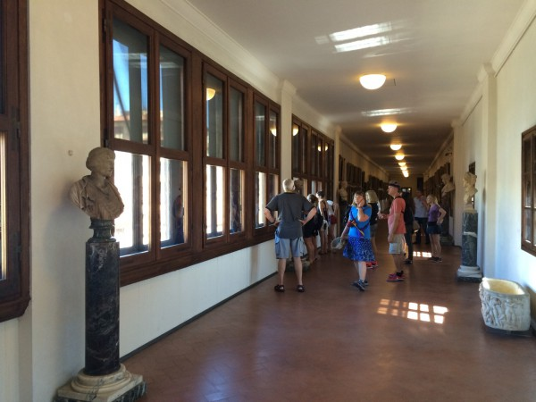 Our tour group looking at the view out the Mussolini/Hitler windows  in the Vasari Corridor over the middle of the Ponte Vecchio.